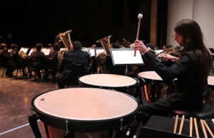 "Robin Bisho plays percussion behind all of the Symphonic Band during ""A Zillion Nickles"" by Samuel Hazo, the opening song for Delta on 6 March 2019 in Atherton Auditorium. Photo by Vivienne Aguilar."