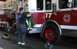 Firefighter Brown gears up at Stockton station. Photo by Ayaana Williams